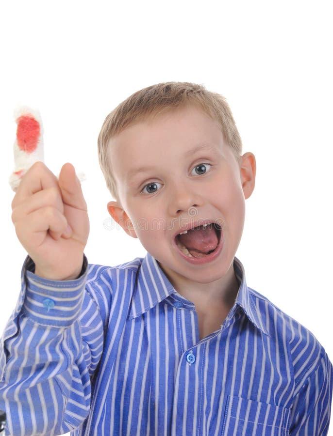 Petit garçon avec un doigt bandé. image stock