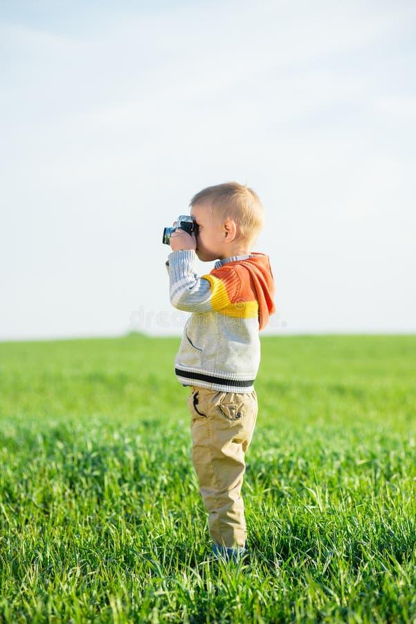 Petit garçon avec un vieux tir d'appareil-photo extérieur image libre de droits