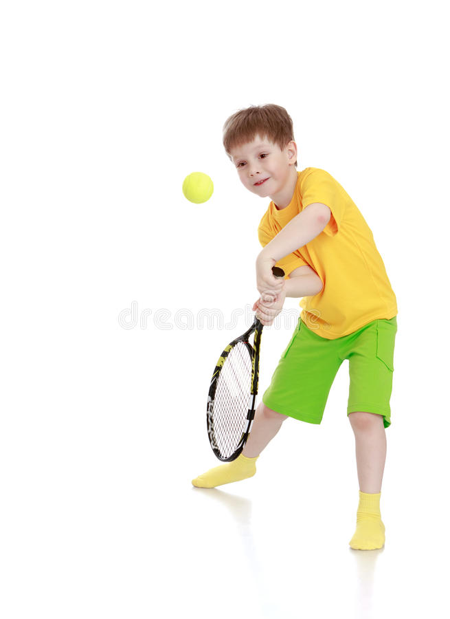Petit garçon avec une raquette de tennis tout en frappant photo libre de droits