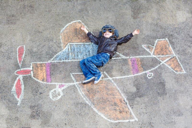 Petit garçon ayant l'amusement avec le dessin de photo d'avion avec la craie illustration stock