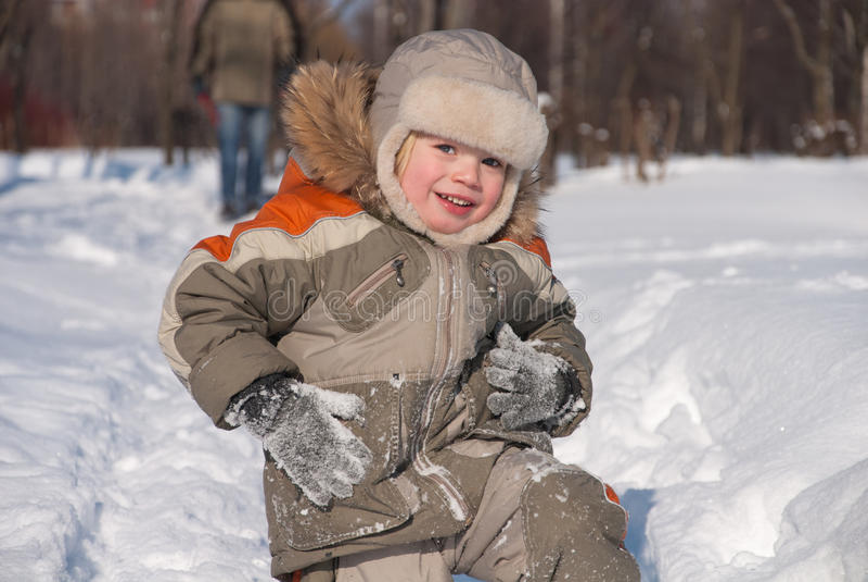 Petit garçon ayant l'amusement dans la neige image stock