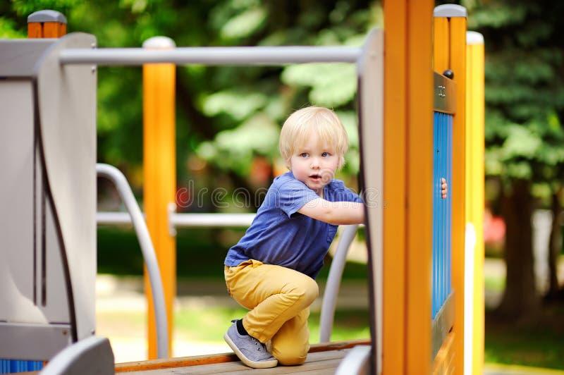 Petit garçon ayant l'amusement sur la glissière extérieure de playground/on photos stock