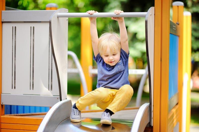 Petit garçon ayant l'amusement sur la glissière extérieure de playground/on photos libres de droits