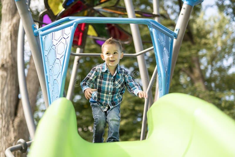 Petit garçon ayant l'amusement sur un terrain de jeu dehors en été Enfant en bas âge sur une glissière images stock