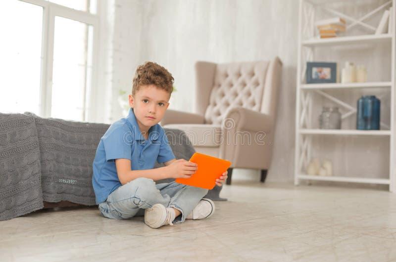 Petit garçon beau aux yeux bleus s'asseyant sur le plancher images stock