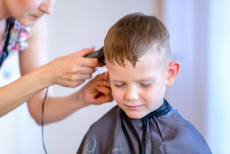Petit garçon beau obtenant une coupe de cheveux image libre de droits