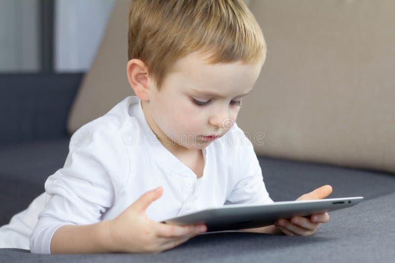 Petit garçon blond à l'aide du comprimé d'écran tactile à la maison Cours d'enfant futé heureux ou jeu de observation de jeu sur  photographie stock libre de droits