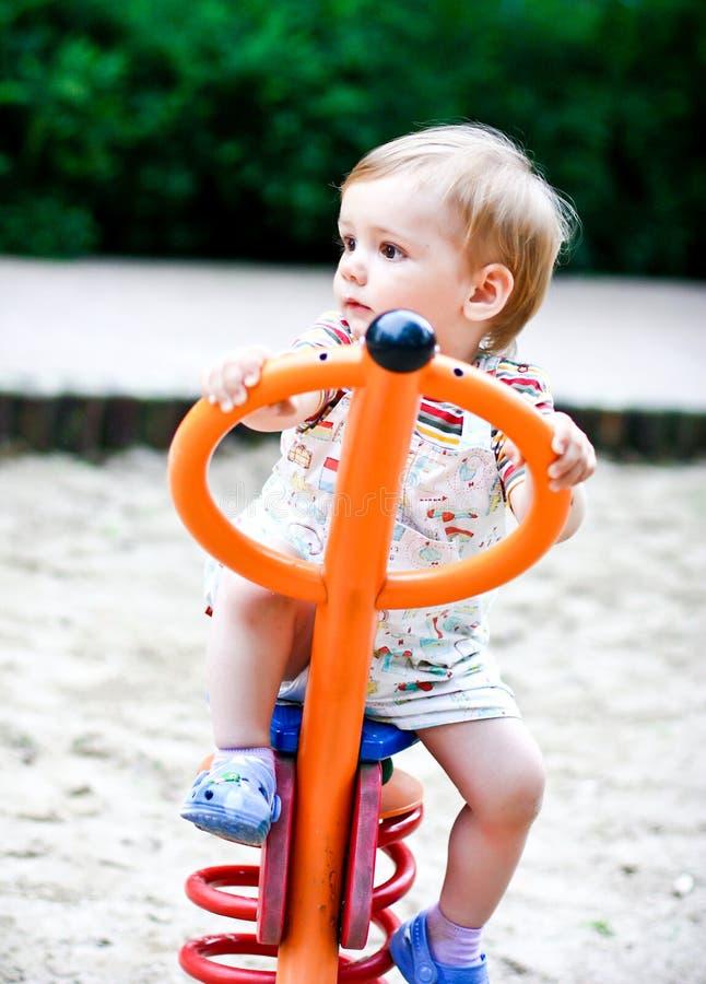 Petit garçon blond jouant sur l'oscillation. Été photo stock
