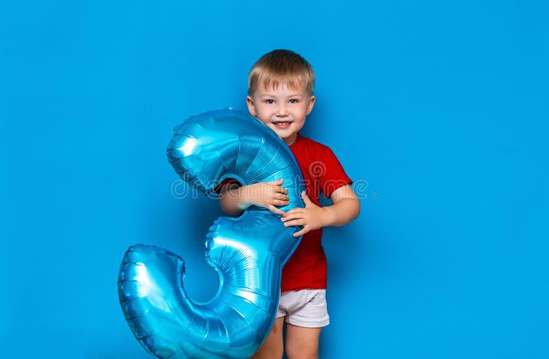 Petit garçon blond mignon sur le fond bleu tenant la couleur bleue de baloon aluminium-enduit de sphère joyeux anniversaire trois photographie stock