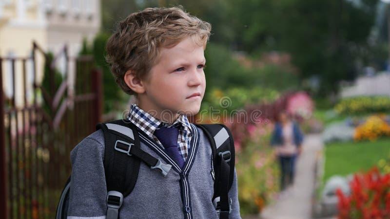 Petit garçon bouclé caucasien dans l'uniforme scolaire avec le sac à dos examinant la distance tenant le territoire proche d'écol photo stock