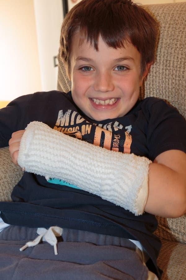 Petit garçon caucasien avec le bras cassé image stock