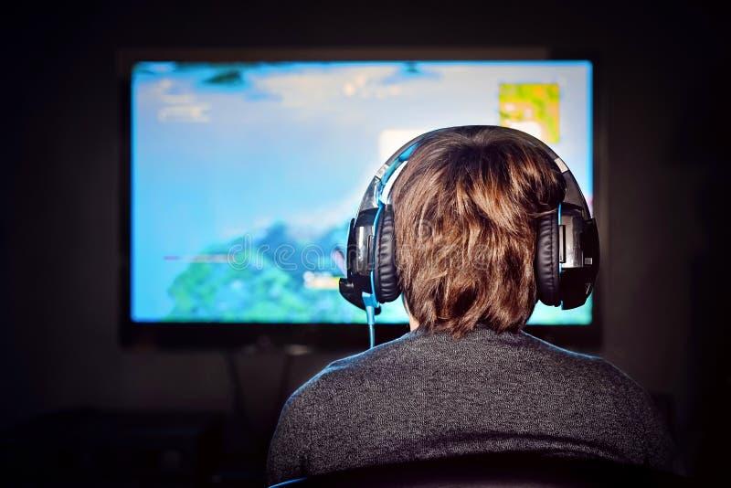 Petit garçon caucasien de gamer portant un jeu vidéo de jeux de casque photo stock