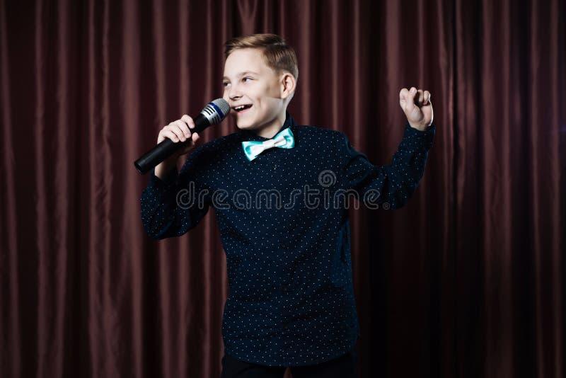 Petit garçon chantant dans microphone enfant dans le karaoke photographie stock