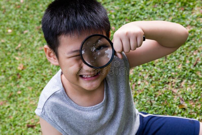 Petit garçon chinois asiatique heureux regardant par la loupe photos libres de droits