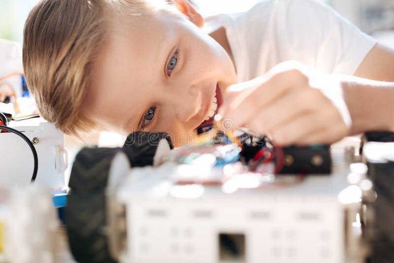 Petit garçon comblé tenant les fils robotiques de véhicule image stock