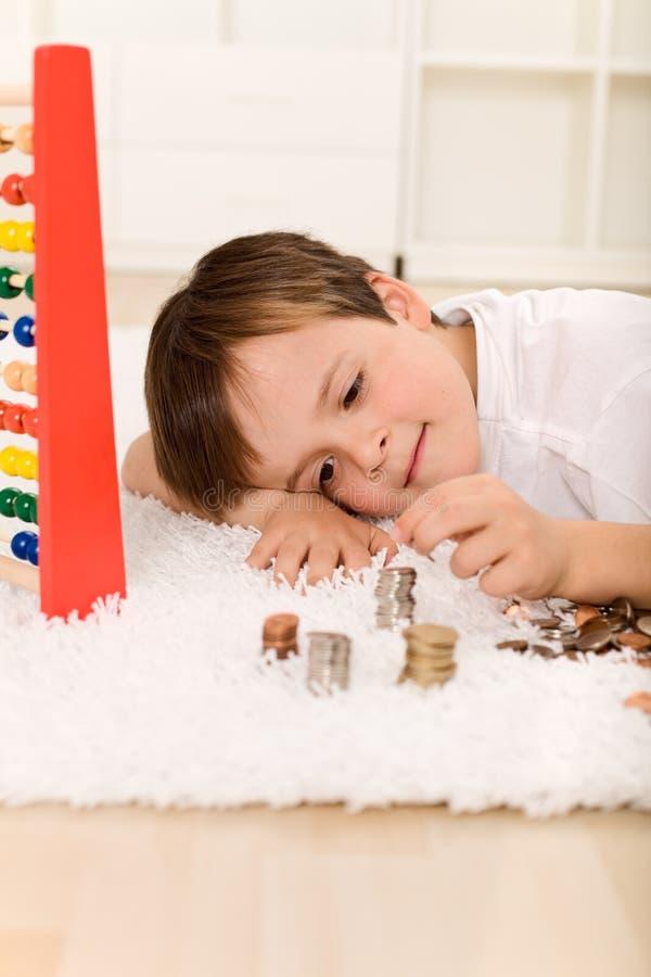 Petit garçon comptant son argent photo libre de droits