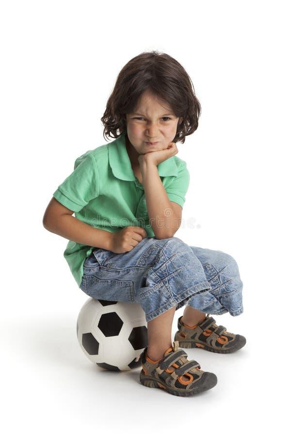 Petit garçon déçu s'asseyant sur une bille de football photos stock