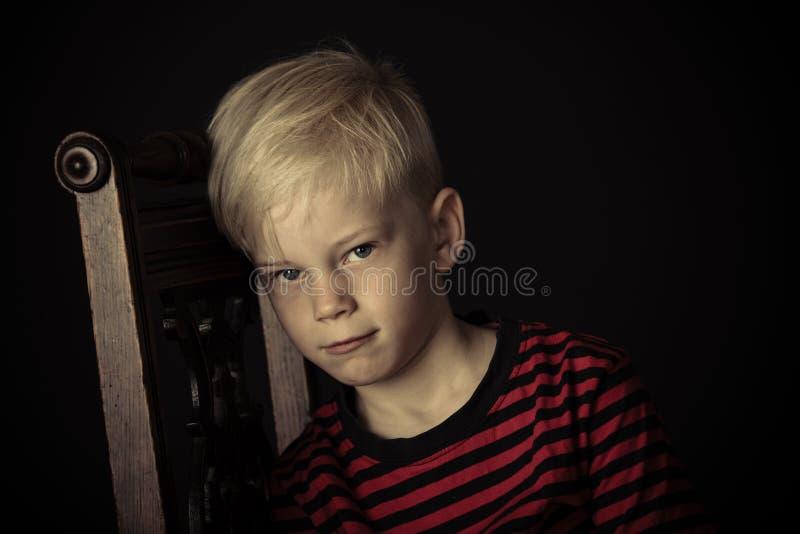 Petit garçon déprimé boudeur s'asseyant sur une chaise photos stock