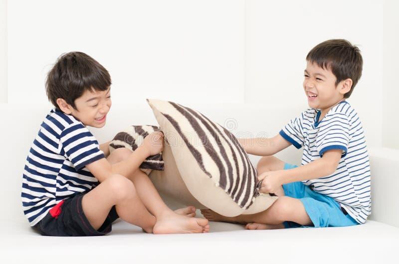 Petit garçon d'enfant de mêmes parents jouant l'oreiller combattant sur le sofa image libre de droits