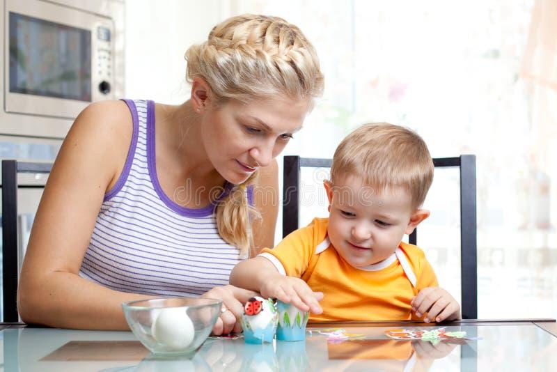 Petit garçon d'enfant en bas âge et sa mère ayant l'amusement avec préparer des oeufs pour la chasse à oeuf de pâques, action tra photos stock