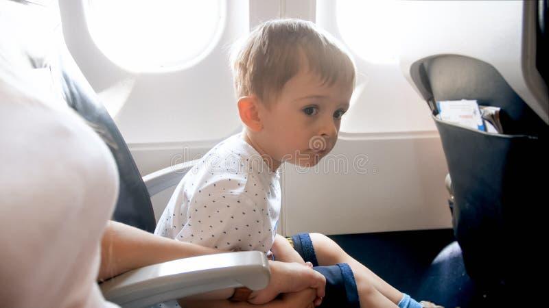 Petit garçon d'enfant en bas âge tenant à la main sa mère pendant le premier vol dans l'avion images libres de droits