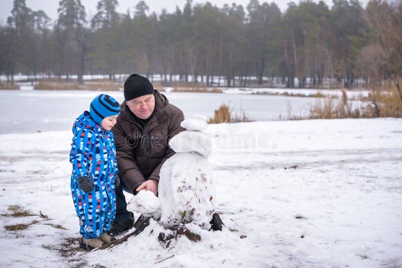 Petit garçon d'enfants de mêmes parents faisant un bonhomme de neige avec le grand-père, jouant et ayant la neige d'amusement, de photographie stock