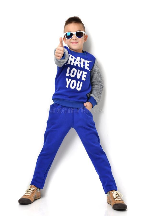 Petit garçon dans des jeans bleus de tissu de lunettes de soleil tenant et donnant le Th images stock