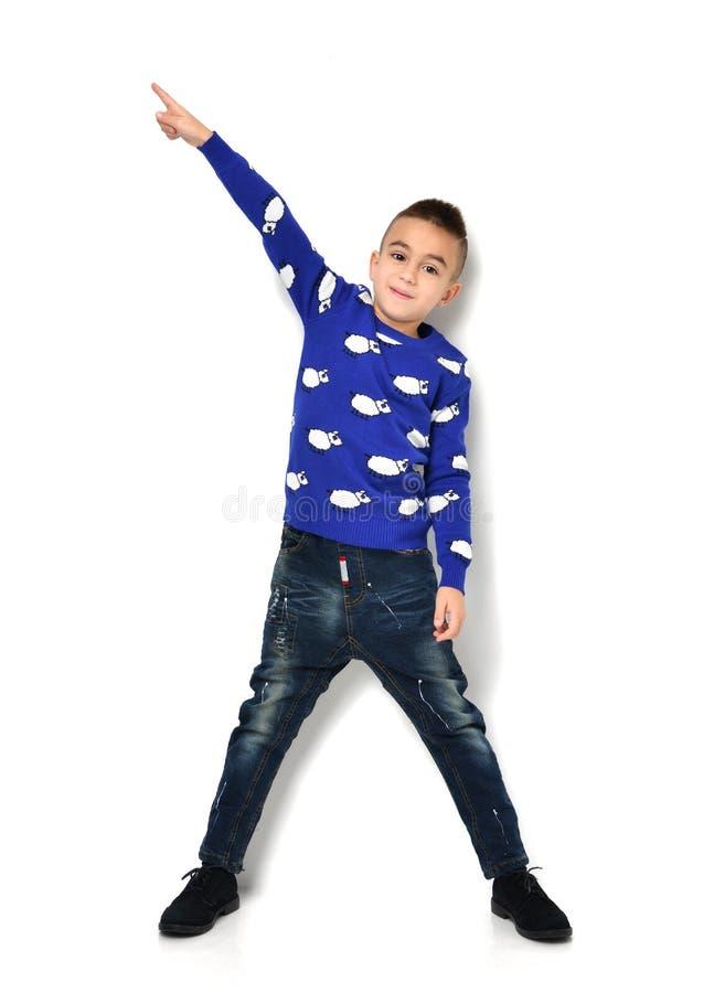 Petit garçon dans des jeans bleus de tissu tenant et dirigeant le doigt à t photographie stock