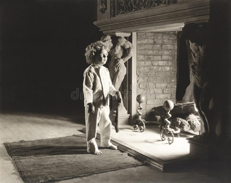 Petit garçon dans des pyjamas par la cheminée tenant le bas de Noël photo stock