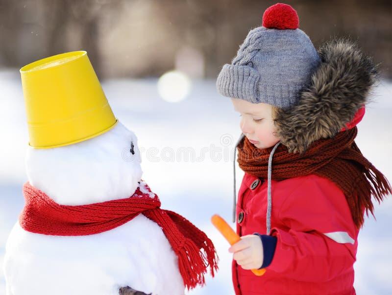 Petit garçon dans des vêtements rouges d'hiver ayant l'amusement avec le bonhomme de neige dans la neige images stock