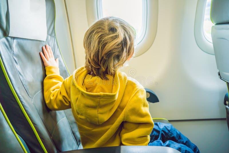 Petit garçon dans l'avion regardant la fenêtre photos libres de droits