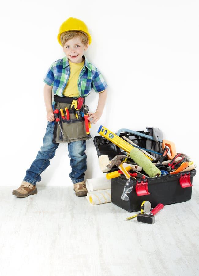 Petit garçon dans le casque antichoc : les outils ceinturent et enferment dans une boîte photographie stock