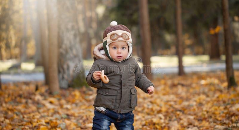 Petit garçon dans le chapeau pilote jouant avec l'avion de jouet en parc Automne photo libre de droits