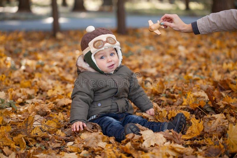 Petit garçon dans le chapeau pilote jouant avec l'avion de jouet en parc Automne image stock