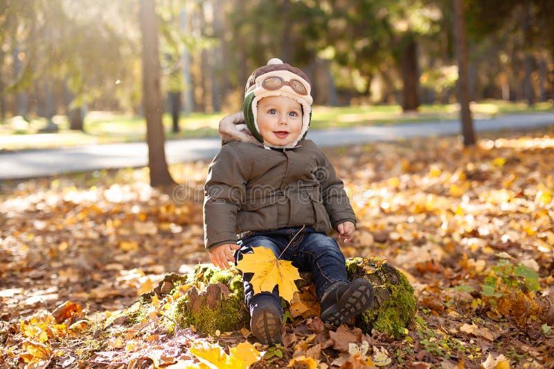 Petit garçon dans le chapeau pilote se reposant sur le feuillage de tronçon, jaune et orange autour de lui Automne images libres de droits