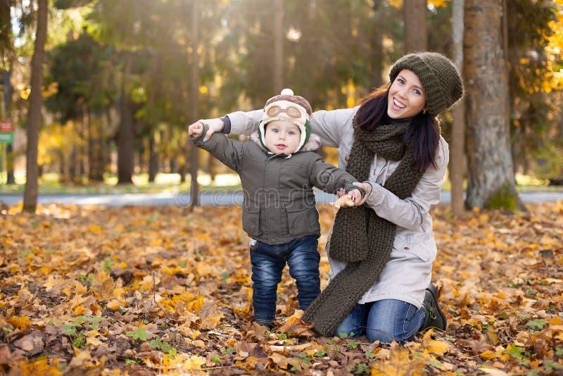 Petit garçon dans le chapeau pilote se tenant avec sa mère et montrant le feuillage d'ailes, jaune et orange autour de lui Automn photo stock