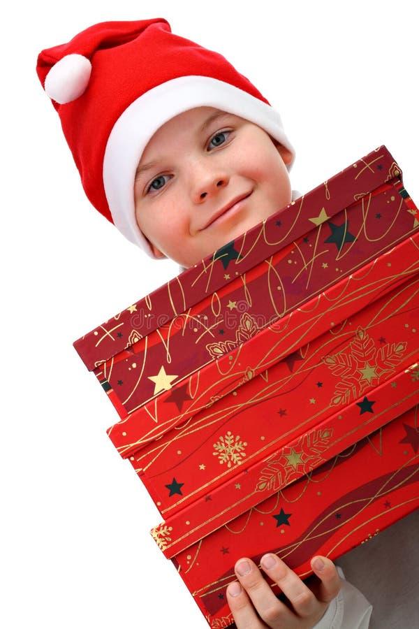 Petit garçon dans le chapeau rouge de Santa portant trois présents image stock