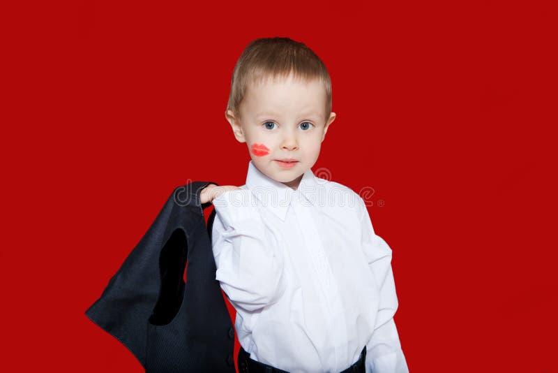 Petit garçon dans le costume avec la trace de baiser sur la joue avec images stock