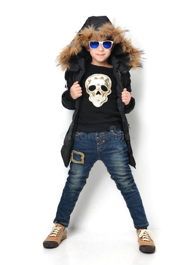 Petit garçon dans les jeans et des lunettes de soleil bleus s de veste d'habillement d'hiver images stock
