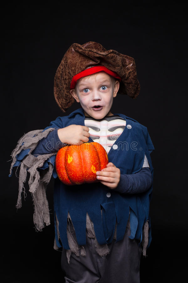 Petit garçon dans un costume de pirate pour Halloween sur un fond noir image stock