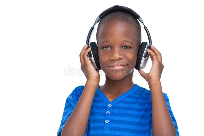 Petit garçon de sourire écoutant la musique photo libre de droits