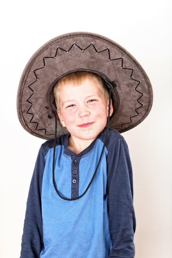 Petit garçon de sourire avec la chemise bleue et le grand chapeau brun images libres de droits
