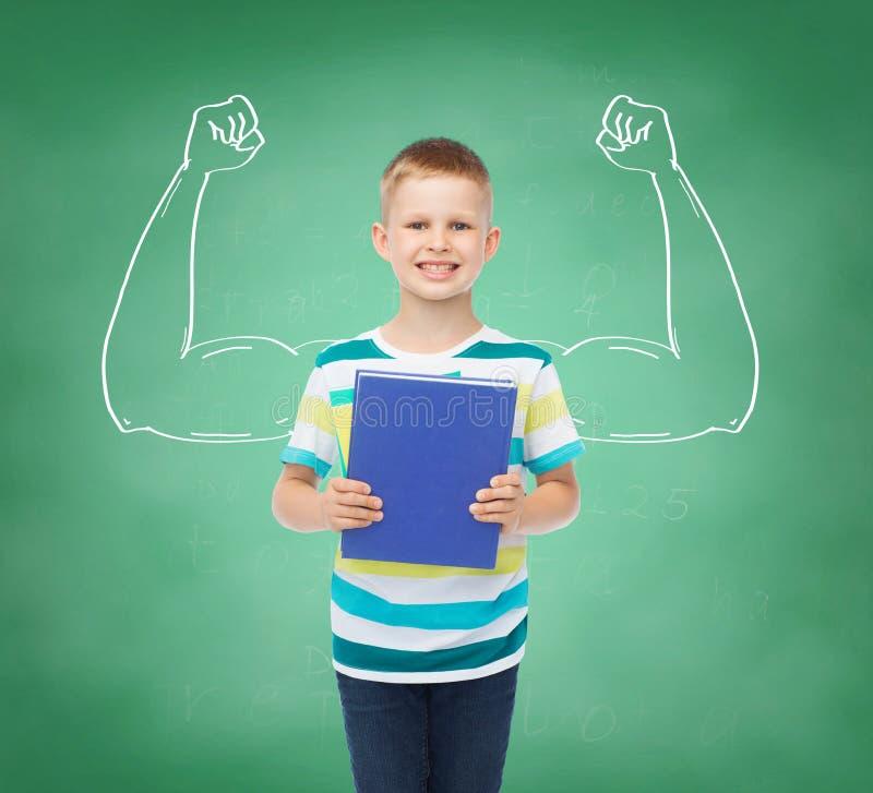 Petit garçon de sourire d'étudiant avec le livre bleu photographie stock libre de droits