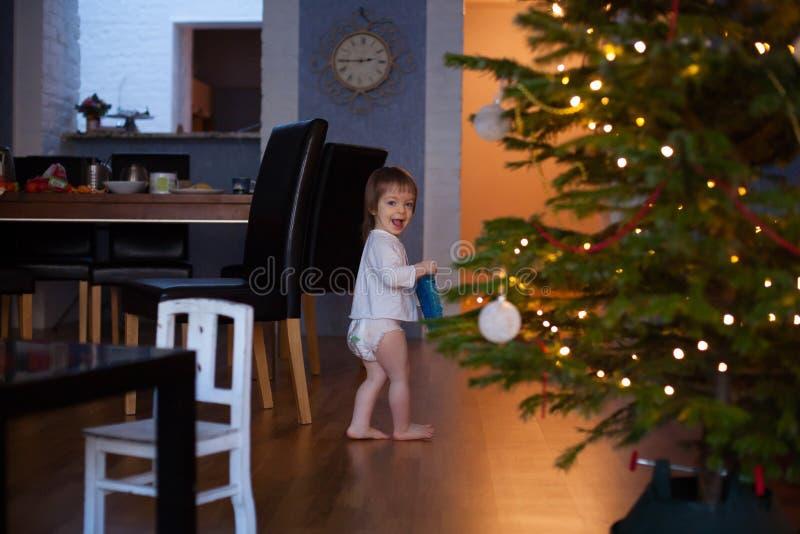 Petit garçon de sourire drôle d'enfant tenant l'arbre de Noël images stock
