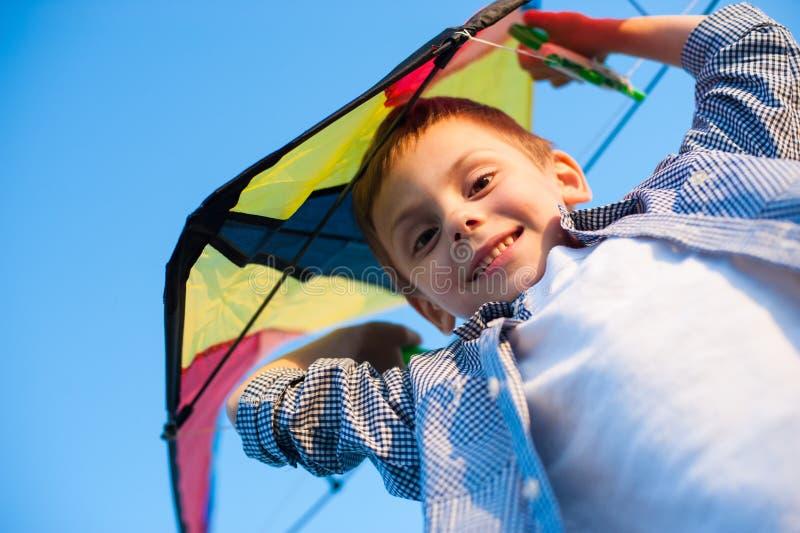 Petit garçon de sourire heureux avec le cerf-volant de jouet au-dessus de la tête sur le fond de ciel bleu dans le jour ensoleill photo libre de droits