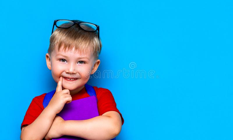 Petit garçon de sourire heureux avec les verres sur sa tête, livre dans des mains, cartable sur ses épaules De nouveau ? l'?cole  photographie stock