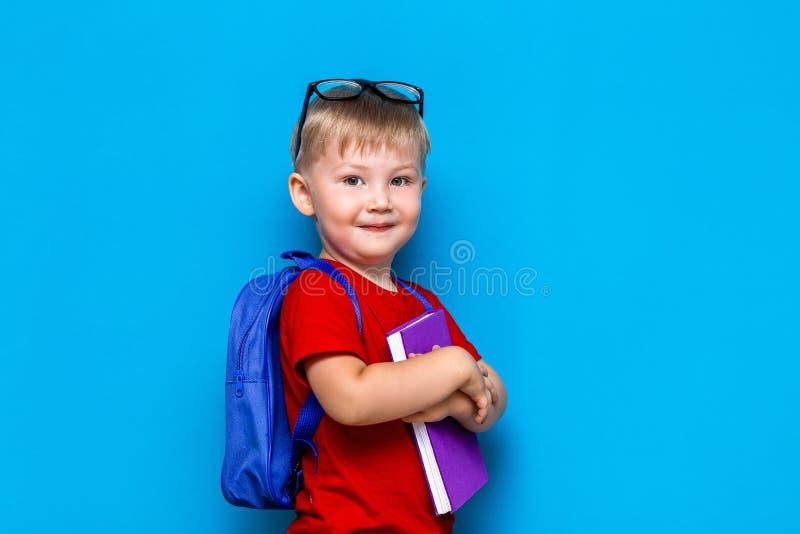 Petit garçon de sourire heureux avec les verres sur sa tête, livre dans des mains, cartable sur ses épaules De nouveau ? l'?cole  photographie stock libre de droits
