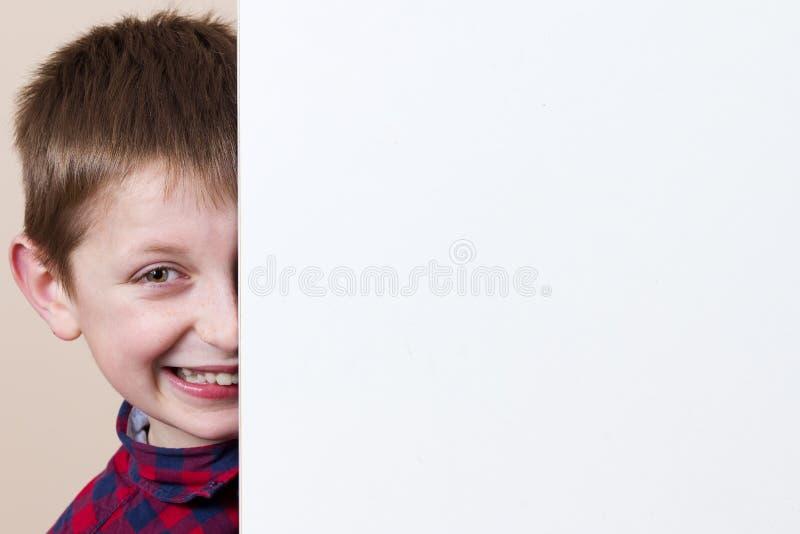 Petit garçon de sourire heureux, montrant la plaquette vide blanche, panneau, position photographie stock libre de droits
