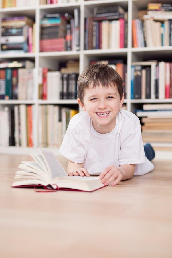 Petit garçon de sourire lisant un livre à la maison photos libres de droits