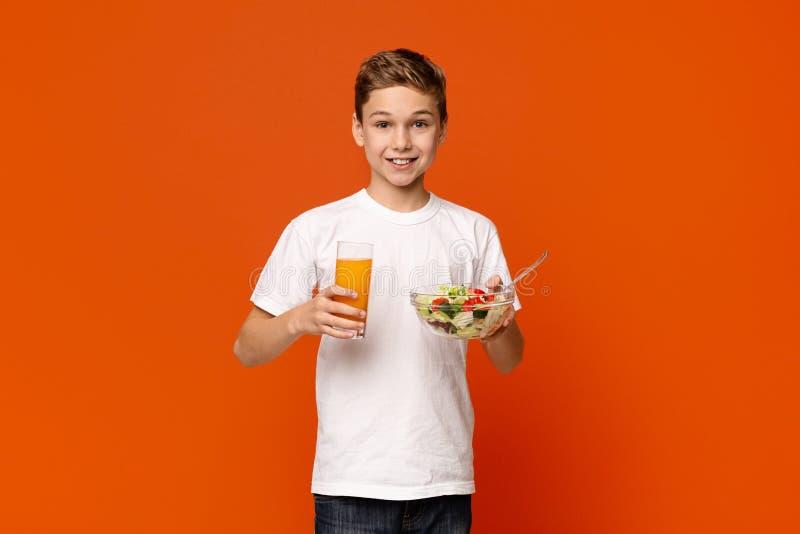 Petit garçon de sourire mangeant de la salade et du jus d'orange végétaux image stock